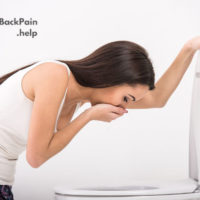 Woman suffering from Nausea and lower back pain